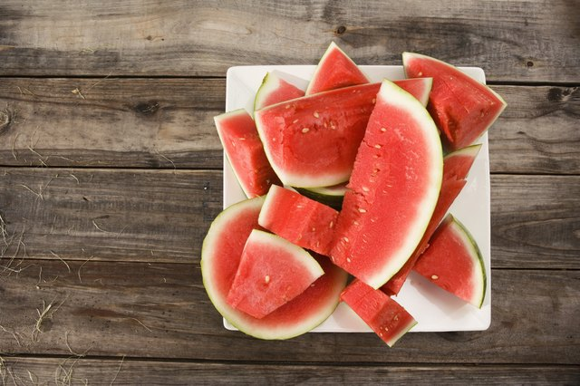 A plate of sliced watermelon on a wooden table