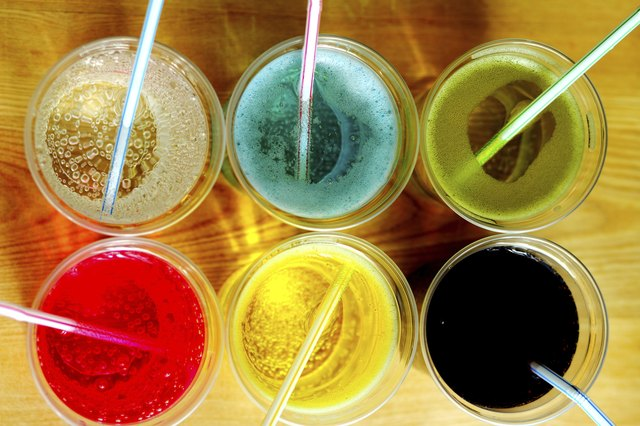 A high angle view of multi-colored soda in glasses with straws.