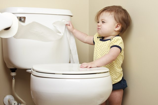 A toddler pulls on a toliet paper roll.