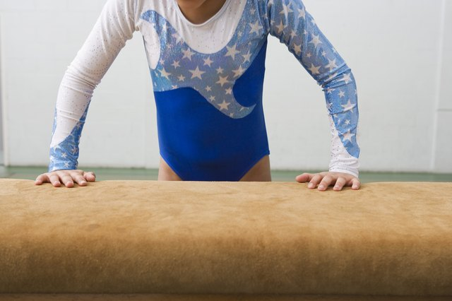 Girl jumping on to balance beam