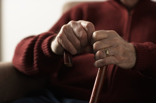 A senior man's hands on the top of a cane