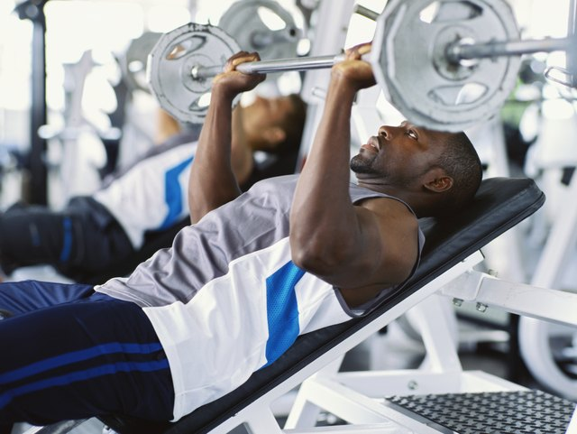 Men exercising with weights at a gym