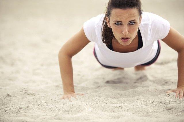 A woman exhaling while doing a push-up on the beach.