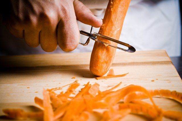 A chef peels a carrot.