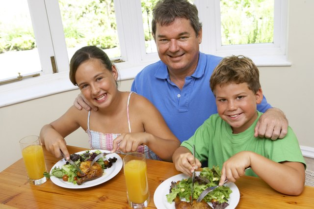 A father makes chicken and salad for his two children for dinner.