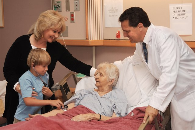 An ill senior woman is visited by her daughter, grandson and doctor in a hospital room