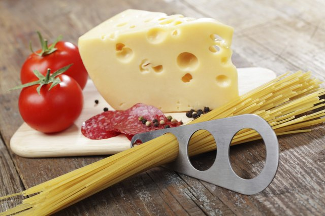 Spaghetti measure tool with cheese, tomato and salami