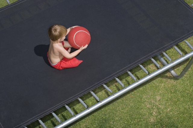 High angle view of toddler on a trampoline with a red ball.