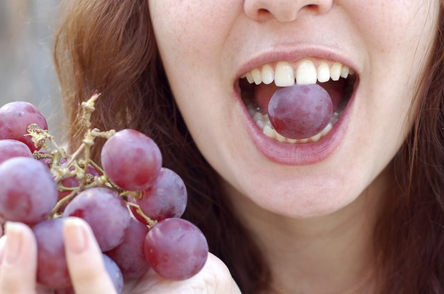 Woman with red grape in her mouth