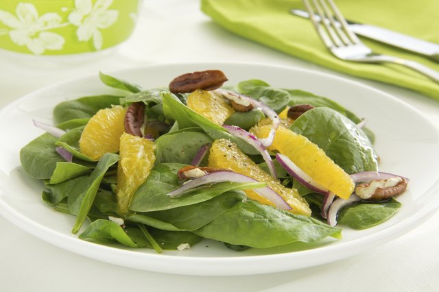 A spinach salad with oranges, red onions, and pecans.