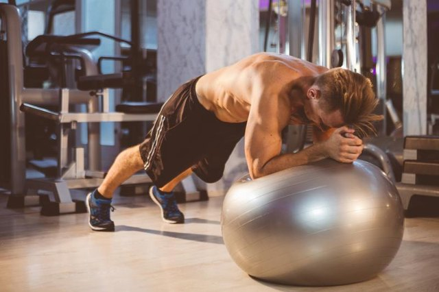 This exercise uses a stability ball to increase the challenge of a standard plank.