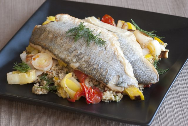 An entree of baked sea bass on a bed of couscous and vegetables.