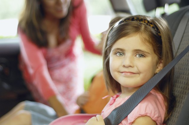 A little girl sits in a booster seat that allows head support against the backseat.