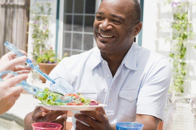 A smiling man eats a salad on the patio.