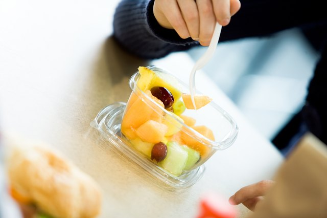 A man eats a container of fresh fruit at a table.