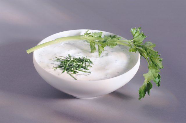 Yogurt in bowl with leaf and greens.