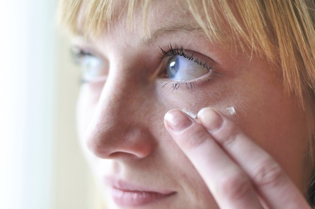 A woman applies moisturizer to the skin underneath her eye.