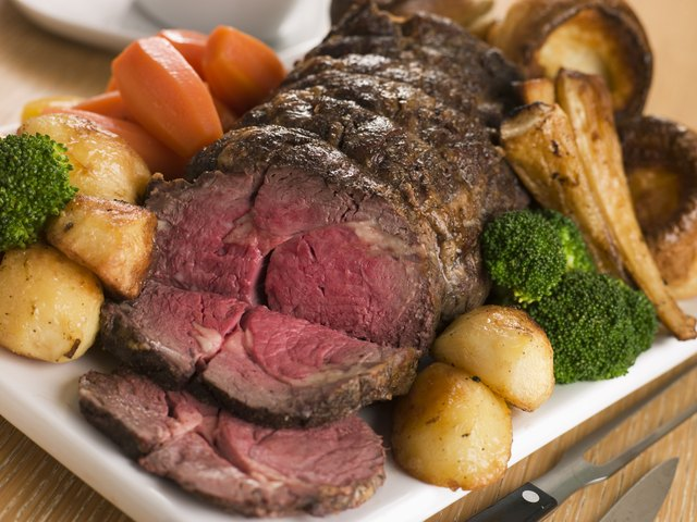 A medium rare beef roast served with roasted potataes, carrots, broccoli and parsnips.