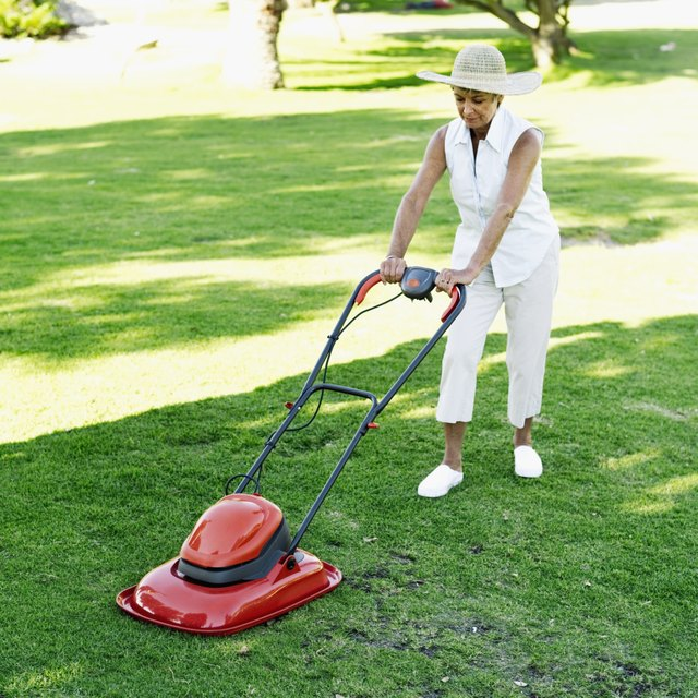 Mature woman push mowing a lawn.
