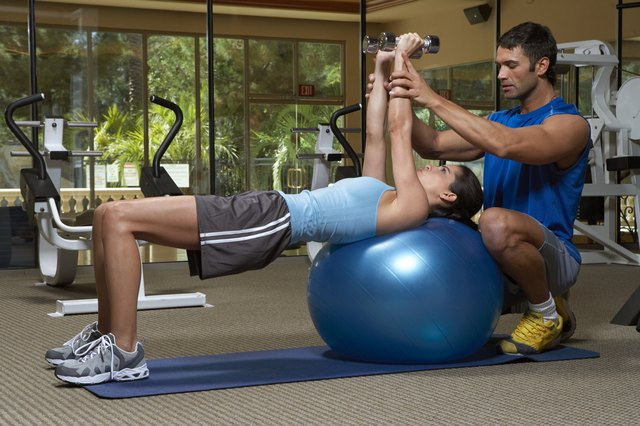 Male instructor training female at a gym with hand weights.