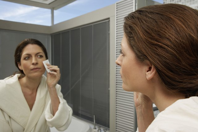 A woman removes make-up from her face in the bathroom mirror.