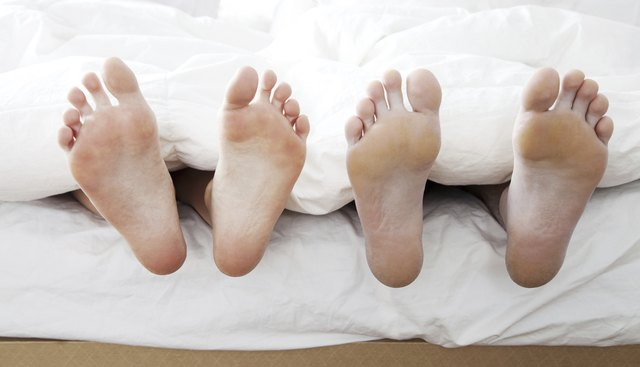 two sets of feet in a bed