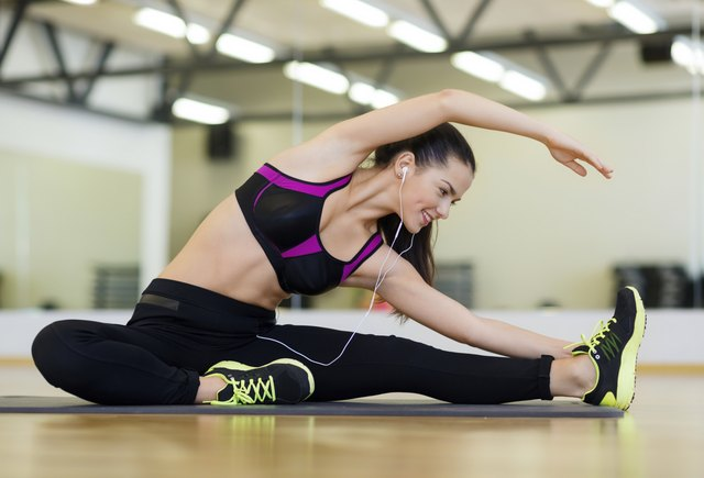A woman listens to music while stretching in a studio at the gym.