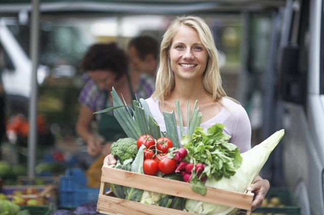 Woman holding box of vegetables at farmer's market