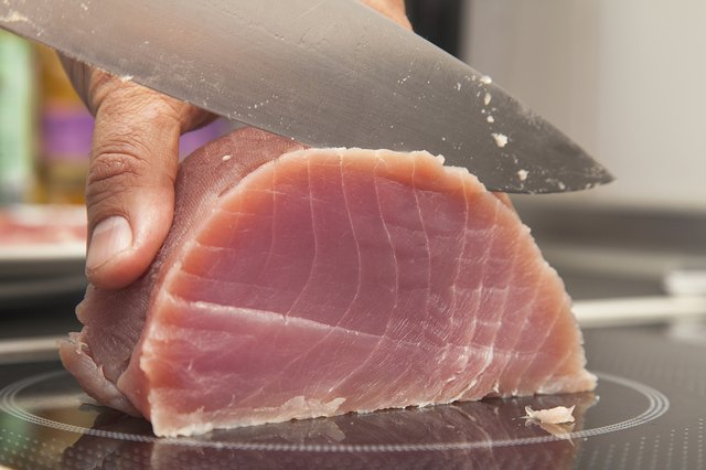 A chef slices fresh raw tuna with a knife.