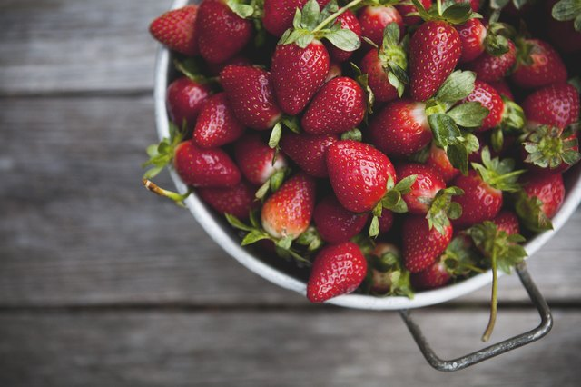 Fresh strawberries in a colander on a picnic table.