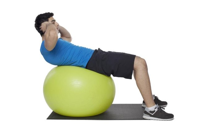 A man performing a mini crunch on a stability ball.
