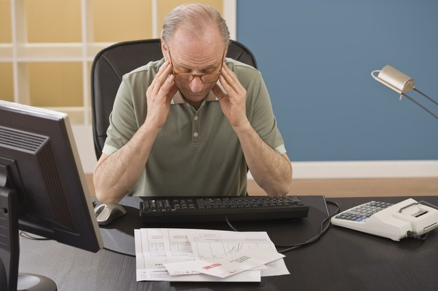 Man with a headache while sitting at his desk.