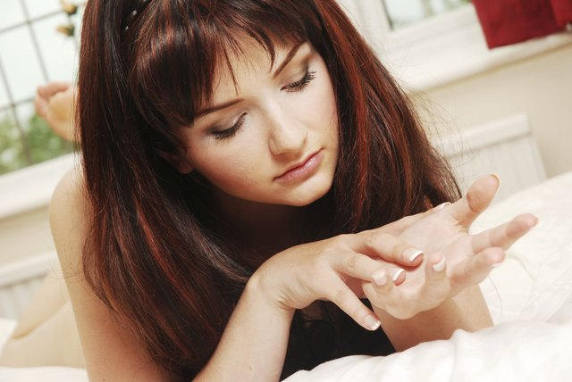 Young woman examining her dry skin.