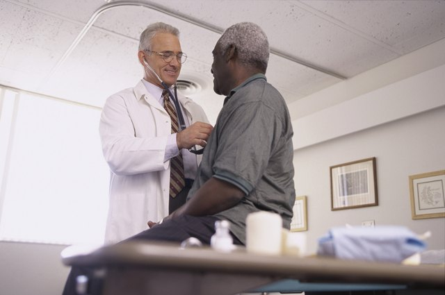 Doctor speaking with a patient while listening to his heartbeat.