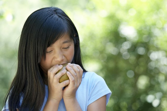 woman taking a bite of a pear