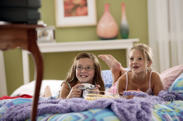 Two girls eat popcorn while watching a movie together at home.
