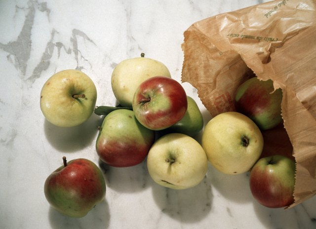 Apples spilling from a paper bag