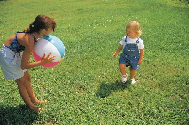 Toddler and adult playing with a beach ball outdoors.