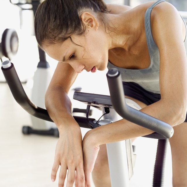 Fatigued woman on exercise bike