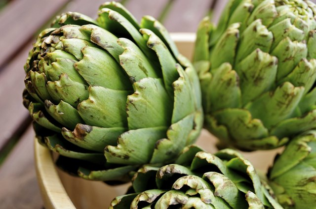Uncooked artichokes in bowl