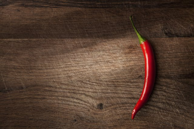A chili pepper on a wood table.