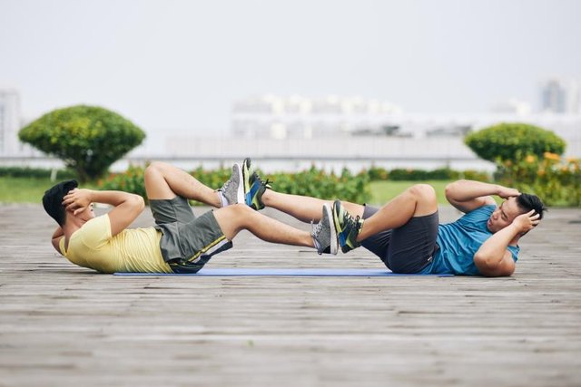 Two men doing bicycle crunches.