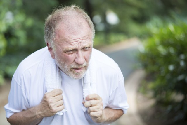 Older man feeling tired and exhausted while walking outside