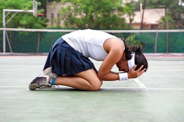 Young woman kneeling on outdoor tennis court.