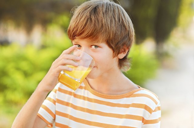 child drinking glass of orange juice