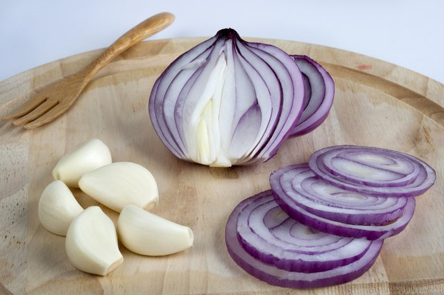 Garlic cloves and slices of an onion on a cutting board