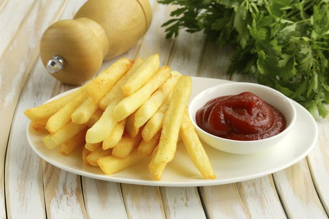 A plate of fries on a cafe table with ketchup and a salt shaker.