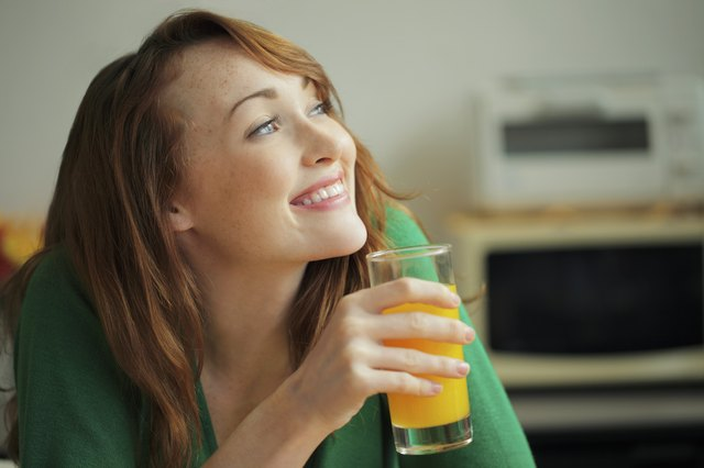 Woman drinking drink in a kitchen.