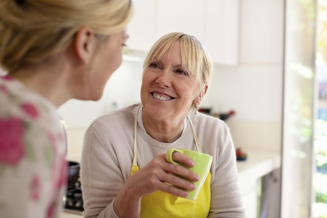 A mother talks to her daughter in the kitchen while drinking a cup of coffee.