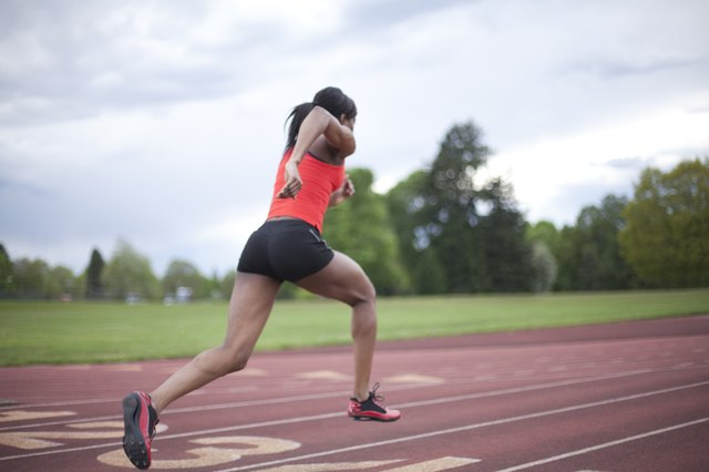 A runner pumps her arms at her side on a track.